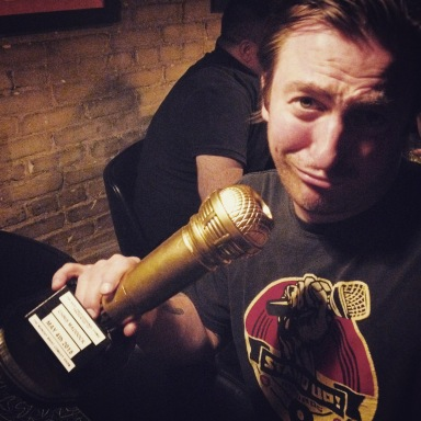 """Chris """"Madoo"""" Maddock gets a big gold phallic award from the Monday Night Comedy Show"""